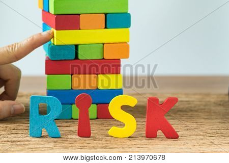 Business risk concept with selective focus on alphabets RISK and hand pulling colorful wooden block tower.