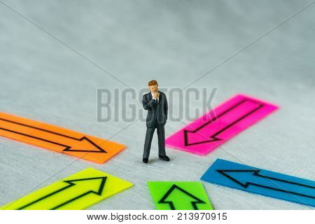 Miniature people figure businessman thinking and standing at the center of arrows pointing to him in all directions as business decision or people center concept.