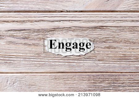 ENGAGE of the word on paper. concept. Words of ENGAGE on a wooden background.