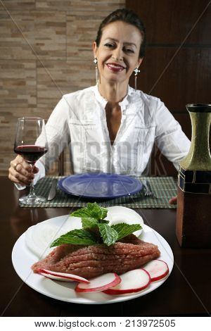 Woman in restaurant eating raw quibe
