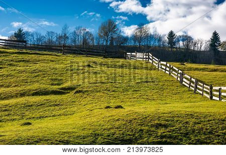 Wooden Fence On Grassy Hillside In Autumn