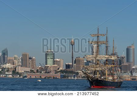 Sydney Australia - March 26 2017: Sailing tall black and red ship with downtown skyline in background on blue water and under clear skies.