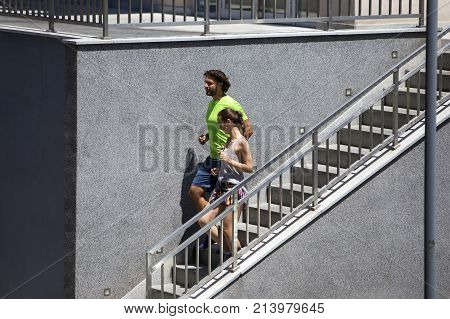 Young Couple Running Down Stairs In Urban Enviroment