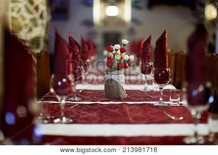The restaurant .Empty restaurant. Table setting. Prepare for a banquet. Festive table.s a long table served tablecloths and a bouquet of flowers on the table.