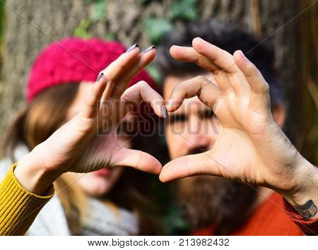 Couple In Love Shows Heart Sign With Fingers.