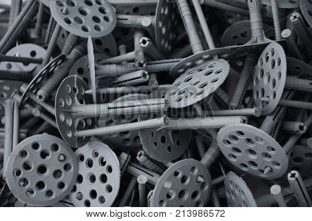 Background Pattern Of Many Gray Plastic Dowels (fastening) For Thermal Insulation. A Huge Pile Of Fi