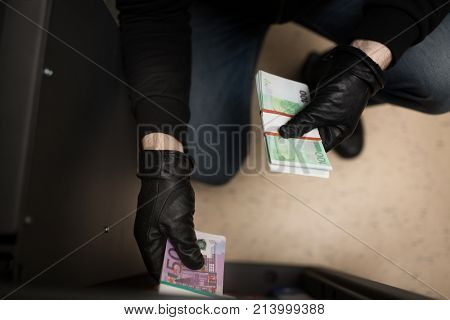 theft, burglary and people concept - thief stealing money from safe at crime scene