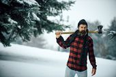 Man with beard in winter forest with snow hold axe. Christmas hipster lumberjack with ax in wood.. Wanderlust hiking and travel. New year man in snowy cold forest. Winter holiday and celebration. poster