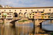 The Ponte Vecchio over the river Arno on the medieval city of Florence in Italy poster