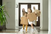 Happy family with kids bought new home, excited children funny girl and boy holding boxes running into big modern house, helping parents with belongings, moving day concept, mortgage and relocation poster