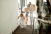 Happy children going upstairs inside two story big house, excited kids having fun stepping walking up stairs running to their rooms while parents holding boxes, family moving in relocating new home poster