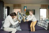Pillow fight between father and little son in living room, happy dad and child boy playing on sofa fighting with cushions, daddy laughing having fun with his kid together, leisure activity at home poster