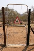 Fence gate to an encloser of a namibian game farm with an Orics warning sign Africa poster