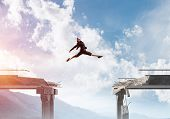 Business woman jumping over huge gap in concrete bridge as symbol of overcoming challenges. Skyscape and nature view on background. 3D rendering. poster