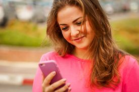 Cute Caucasian young woman with a cellular phone looking at the screen with tender emotion. Tender look stock image.
