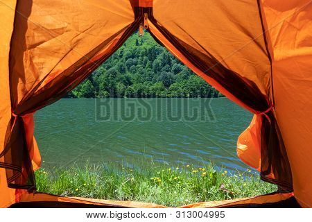 Camping tent at scenic campsite on a lake poster