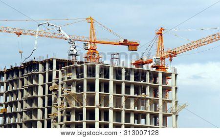 Two Cranes Near Building. Concrete Building Under Construction.