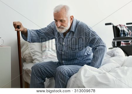 Sad Senior Man With Alzheimer's Disease Holding Walking Stick And Sitting On His Bed In Nursing Home