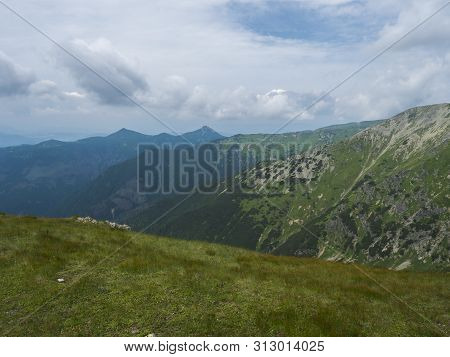Beautiful Mountain Landscape With Lush Green Grass, Meadow And Bare Mountain Peaks On Ridge Western