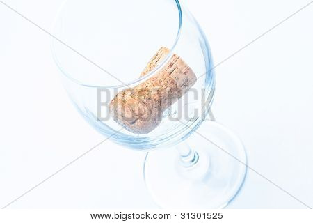 single glass of wine with cork from a bottle
