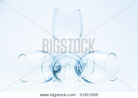 Wine glasses stand and lie symmetrically on white