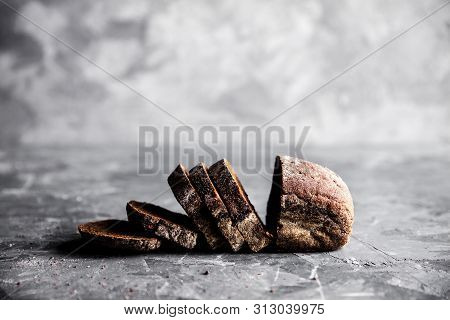 Sliced Homemade White Wheat Bread With Wheat Flour On Old Black Oven Tray As Background. Top View A