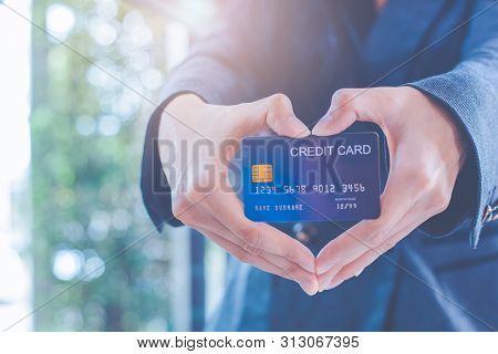 Female Businessmen Are Holding A Credit Card And Making A Heart-shaped Hand.