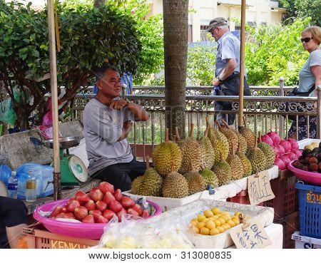 Malacca, Malaysia--febuary 2018:  A Man Sells Assorted Fruits Like Durian, Mango And Others Outside