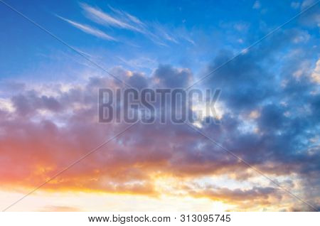 Sunset sky background - pink, orange and blue dramatic colorful clouds lit by evening sunset light. Vast sunset sky landscape scene