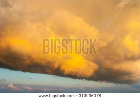 Sunset dramatic sky background - orange dramatic colorful clouds lit by evening sunset light. Vast sunset sky landscape