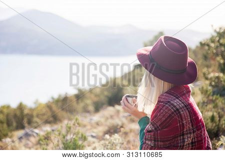 Woman Traveler In Mountains Above Autumn Sea. Cozy Fall Picnic With Coffee On Beach. Girl In Warm Pl