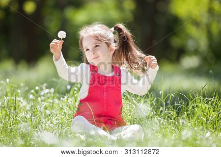 Cute little girl play in the park with flowers. Beauty nature scene with colorful background at summer or spring season. Family outdoor lifestyle. Happy girl relax on green grass