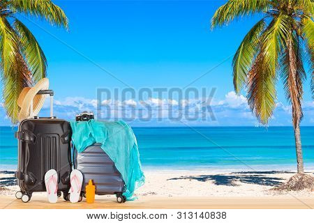 Summer holidays concept. Suitcases baggage with straw hat, blue pareo, flip flops, sunscreen lotion bottle and retro camera against amazing ocean beach with palms and blue sky background. poster