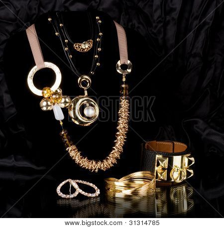 Gold jewelry in precious stones on a black background