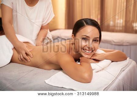 Portrait Of Asian Beautiful Woman Lying On Massage Table And Smiling At Camera While Massage Therapi