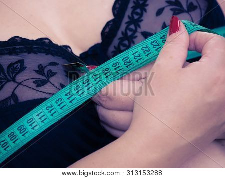 Plus Size Fat Woman Wearing Black Bra Using Tape Measure To Check The Measurements Of Her Big Chest
