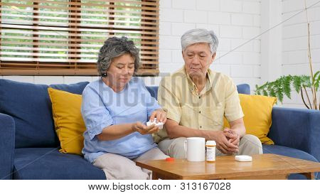 Senior Asian Couple Take Pill Medicine For Elderly Health Care While Sitting On Sofa, Retirement Cou