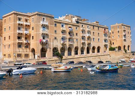 The View Of Residental Houses On The End Of Senglea  Peninsula With The Traditional Maltese Boats Mo