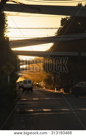 Main street of the downtown of Bonito MS, Brazil. Coronel Pilad Rebua street. Avenue decorated with portals and plants at the sunset. Touristic destination of Bonito city. poster