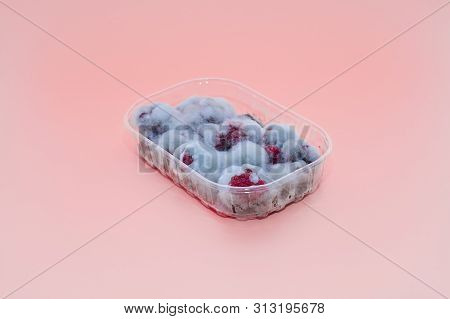 Closeup Of Rotten Moldy Raspberry In Plastic Box Isolated On Pink Background. Damaged Ripe Berry Wit