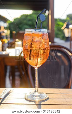 Closeup Wine Glass Of Cold Cocktail Aperol Spritz On Background Of Restaurant. Traditional Italian A