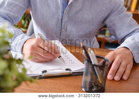 Man Filling Out A Questionnaire On A Wooden Table. Horizontal Composition. Elevated View.