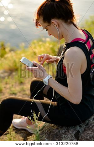 Young Woman Runner Using Smartphone and Listening to Music at Sunset on the Mountain Trail. Training and Sports Concept.