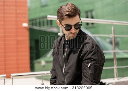 American Young Man Hipster In Stylish Sunglasses In A Vintage Jacket With A Fashionable Hairstyle Is
