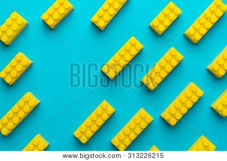 Flat Lay Image Of Yellow Blocks From Child Constructor. Bright Plastic Blocks On Turquoise Blue Back