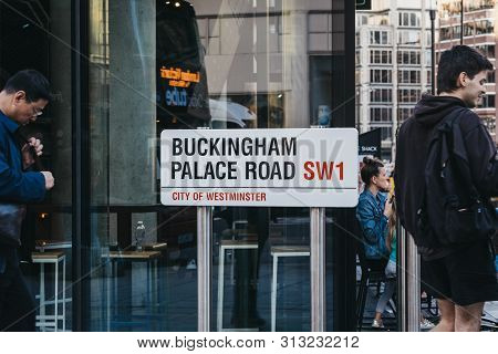 London, Uk - July 15, 2019: People Walking Past Street Name Sign On Buckingham Palace Road, A Famous