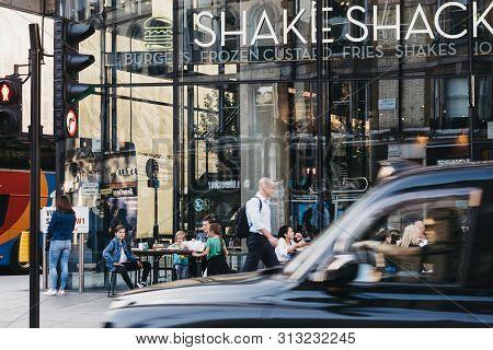 London, Uk - July 15, 2019: Black Cab Driving Past Shake Shack In Victoria Station, Motion Blur. Sha