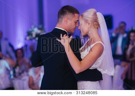 Portrait Of First Dance Of Stylish Wedding Couple. Handsome Groom And Elegant Bride In The Restauran