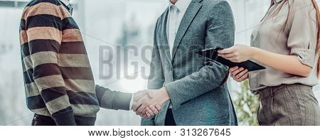 Handshake Of A Manager And A Customer On The Background Of The O