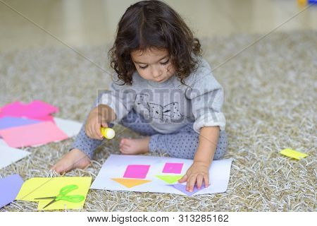 Cute Little Girl Make Applique, Glues Colorful House, Applying A Color Paper Using Glue Stick While
